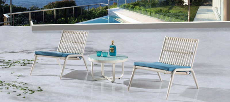Outdoor patio set with armchairs and a white table.