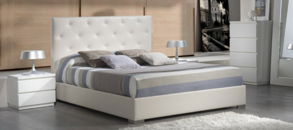 Bed white and grey in bedroom.