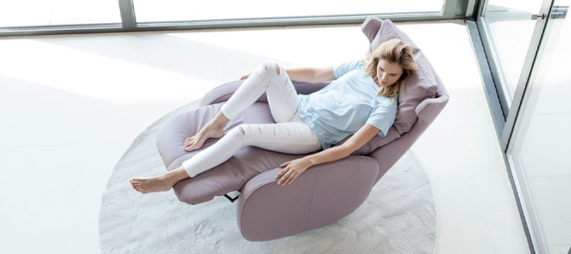 Girl laying down on this comfy armchair by Fama.