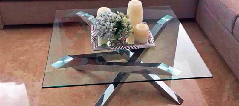 Elegant silver and glass top coffee table in a living room.