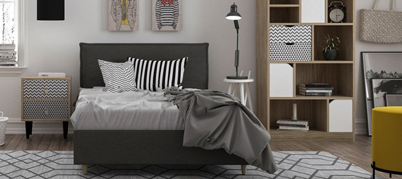 White and black wooden side night table next to a bed in a big bedroom space.