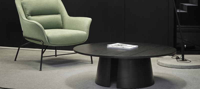 Black coffee table near a green armchair in a living room.
